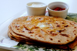 Spicy Aloo Paratha served with curd and pickles with butter topping