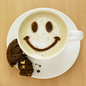 Cappuccino with smiley face and chocolate chip cookie.