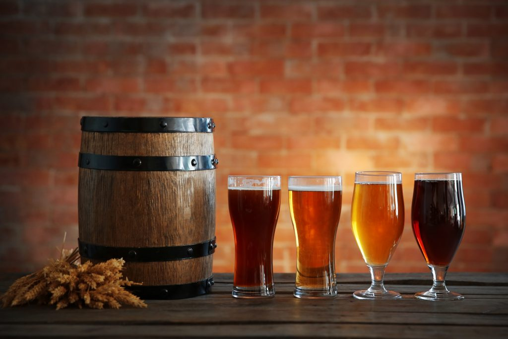 Glasses with different sorts of craft beer, wooden barrel and bar